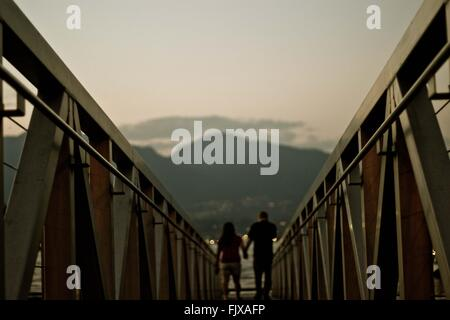 Rear View Of Couple Walking Along Railings - Stock Photo