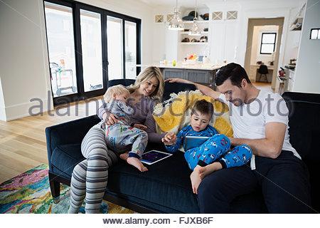 Family in pajamas using digital tablets on sofa - Stock Photo