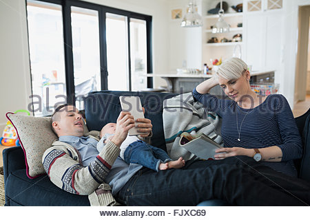 Parents and baby son reading relaxing on sofa - Stock Photo
