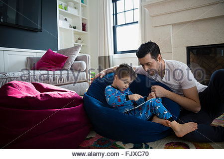 Father and son in pajamas using digital tablet - Stock Photo