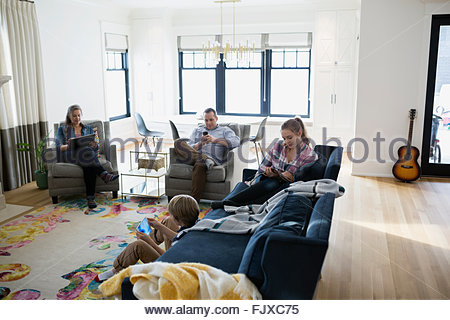 Family relaxing using technology in living room - Stock Photo