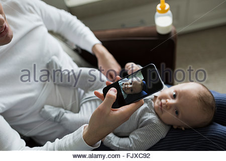 Father photographing baby son on lap camera phone - Stock Photo