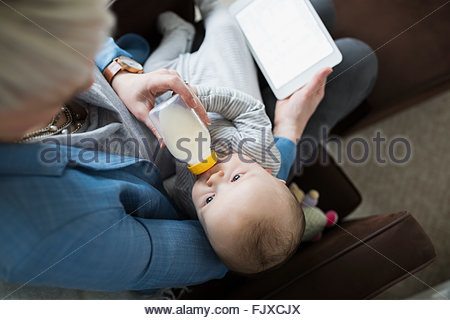 Overhead view mother feeding baby son bottle - Stock Photo