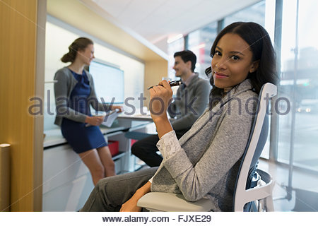Portrait confident young businesswoman in office with coworkers - Stock Photo