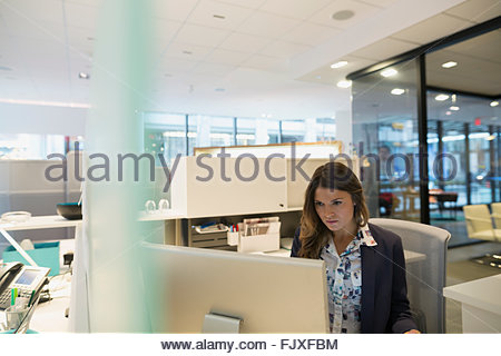 Focused young businesswoman working at computer in office - Stock Photo