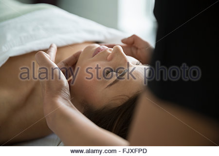 Serene woman with eyes closed receiving spa facial - Stock Photo