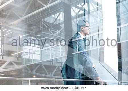 Digital composite businessman looking through modern window - Stock Photo