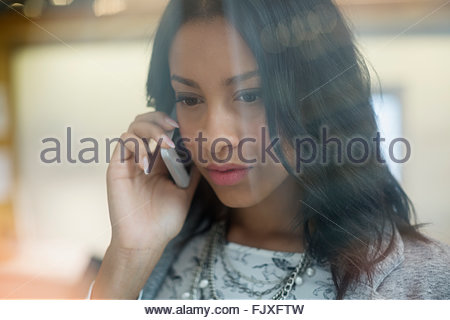 Close up serious young businesswoman talking cell phone - Stock Photo
