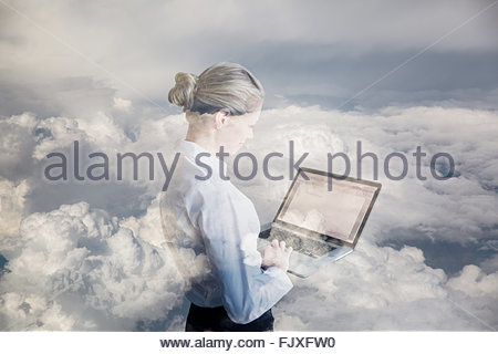 Digital composite businesswoman using laptop in clouds - Stock Photo