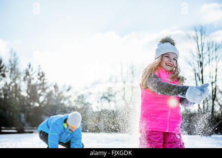 Father and daughter playing snowball fight - Stock Photo