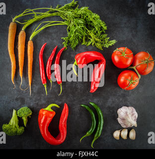 Hot and sweet chilli peppers, Dutch sweet carrots, tomatoes, broccoli, and garlic creatively arranged on grunge - Stock Photo