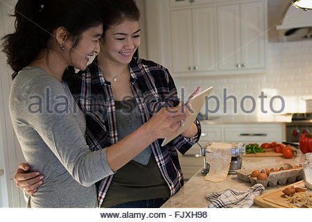Mother and daughter hugging using digital tablet kitchen - Stock Photo