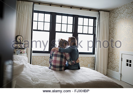 Mother hugging and kissing teenage daughter in bedroom - Stock Photo