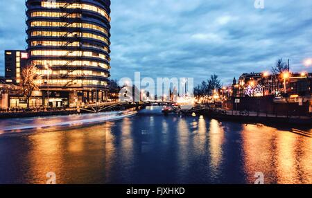 Light Trail Over River In Illuminated City Against Sky At Dusk - Stock Photo