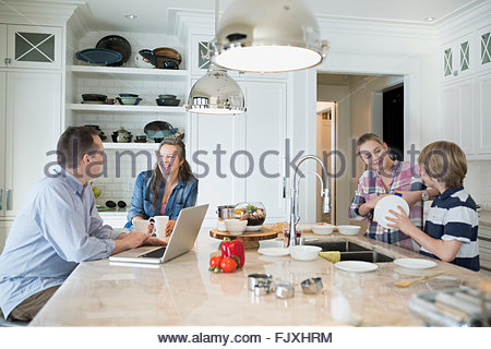 Brother and sister doing dishes while parents talk - Stock Photo