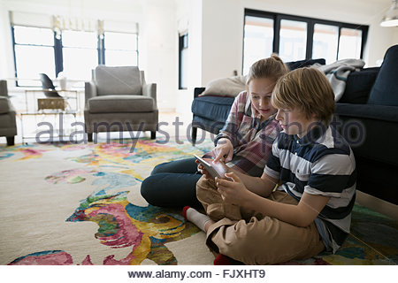 Brother and sister using digital tablet living room - Stock Photo