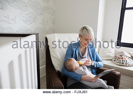 Mother with digital tablet feeding baby son bottle - Stock Photo