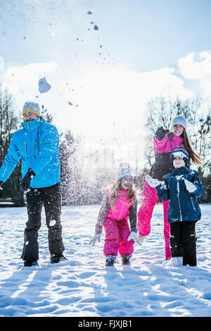 Family throwing snowballs - Stock Photo