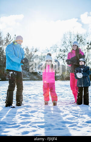 Family holding snowballs - Stock Photo