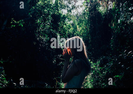 Side View Of Young Woman Against Trees In Forest - Stock Photo