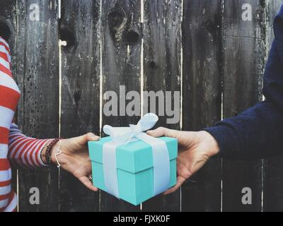 Cropped Image Of Hands Holding Gift Box Against Wooden Fence - Stock Photo