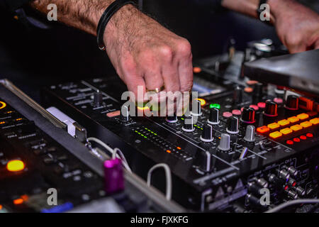 Hands Adjusting Regulators Of A Mixer Unit - Stock Photo