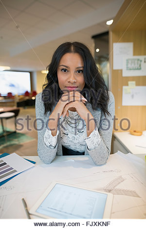 Portrait of confident young female architect at desk - Stock Photo