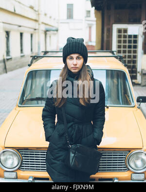 Portrait Of Beautiful Young Woman Leaning On Car Parked At Street - Stock Photo