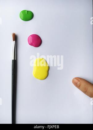 High Angle View Of Paintbrush And Colors On White Paper - Stock Photo