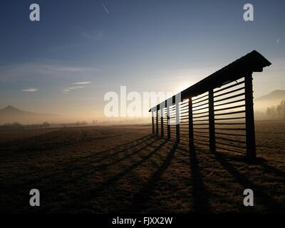 Silhouette Hayrack On Field Against Sky During Foggy Weather - Stock Photo