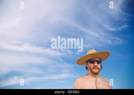 Low Angle View Of Shirtless Mature Man Wearing Hat Against Sky - Stock Photo