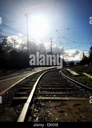 Railroad Tracks On Field By Street Against Sky - Stock Photo