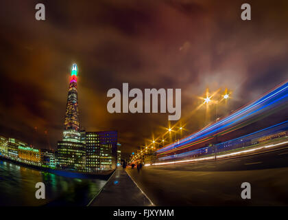 Light Trails On Bridge Over Thames River By Illuminated The Shard Against Sky At Night - Stock Photo