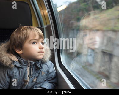 child looking through window. close-up of boy wearing fur jacket looking through car window - stock photo child