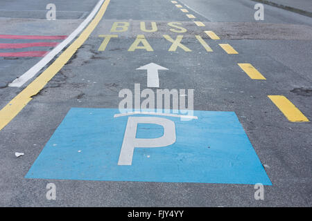 A road in town with signs painted on the ground parking and a bus line. - Stock Photo