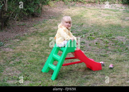 Little blonde girl ,child kid sitting on a small play slide in the garden wearing a yellow raincoat, child playing, alone, lonely