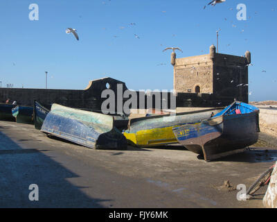 Blue  and yellow fishing boats lying on their sides at Essaouira in Morocco with the old Portuguese fort in the - Stock Photo