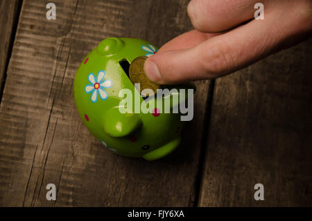Male hand with a coin and a piggy bank on wood, saving money concept - Stock Photo