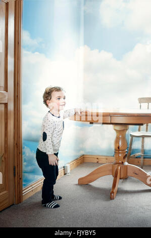 small boy playing around the wooden table in the kitchen - Stock Photo