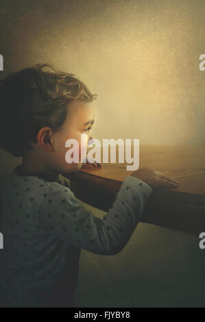 small boy resting his arms on the wooden table - Stock Photo
