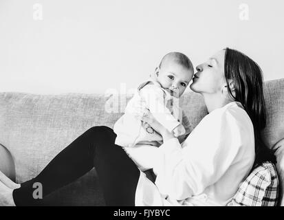 young mom kissing her baby girl on sofa at home - Stock Photo