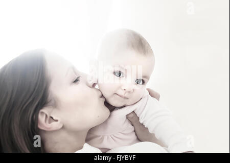 young mum kissing her baby girl in arms - Stock Photo