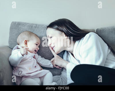 young woman playing with her baby girl on the sofa bed - Stock Photo