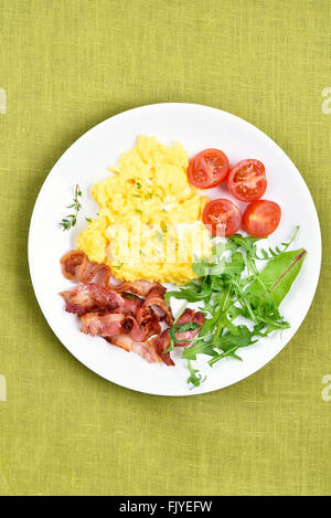 Plate with scrambled eggs, bacon and vegetable salad, top view - Stock Photo