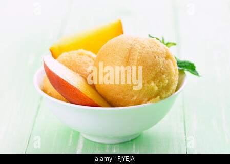 Apricot peach ice cream and slices, close up view - Stock Photo