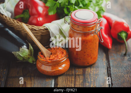 Jar of homemade ajvar, a delicious roasted red pepper and eggplant dish. - Stock Photo