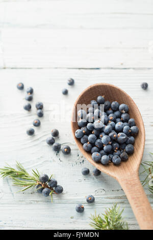 Wooden spoon with juniper berries - Stock Photo