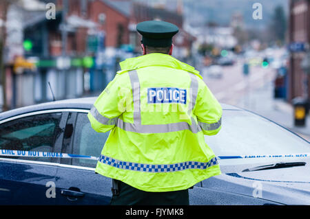 A PSNI Police Officer stands at a police cordon during a bomb alert - Stock Photo