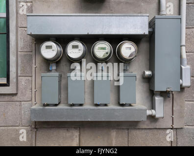 Line up of four electric power meters on side of apartment complex - Stock Photo
