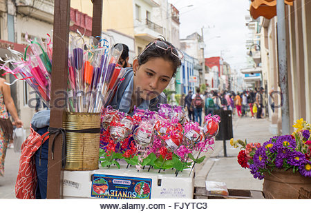 Highschool student picking flowers from a private stand in the boulevard area. - Stock Photo